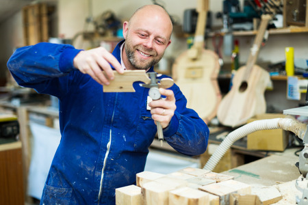 Happy male craftsman working with unfinished guitar indoors photo