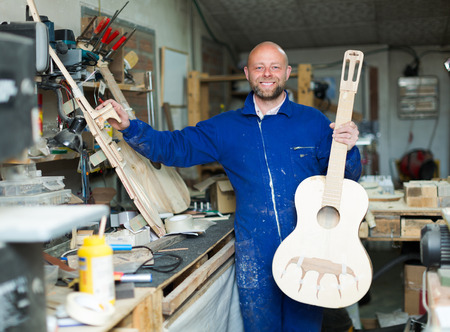 workplace wellness: Positive smiling craftsman working with unfinished guitar at workshop