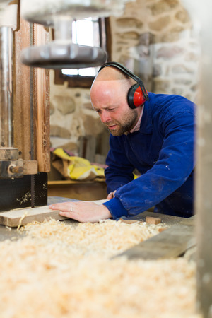 woodcutting: Professional guitar maker working on a woodcutting machine at guitar workshop Stock Photo