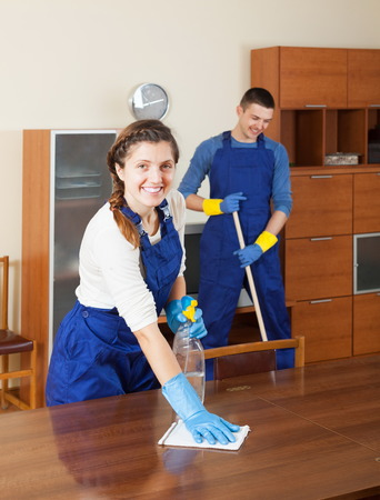 houseman: Smiling cleaners cleaning furniture and floor in room