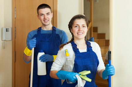 company premises: Happy cleaners cleaning room at home