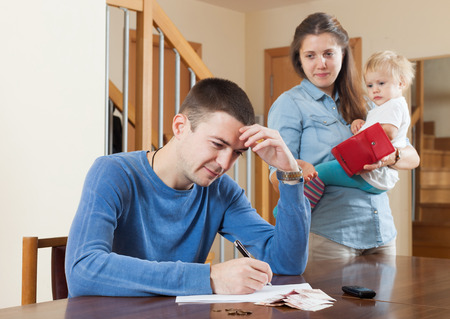 covetous: Depressed woman with baby against husband at table with money at home