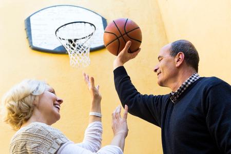 mature people: Happy persone mature che giocano con la palla in cortile