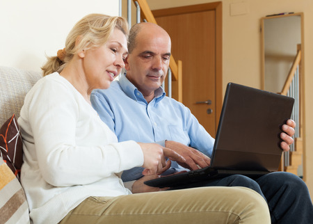 Smiling mature couple  with laptop  in room photo