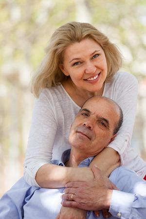 heterosexual: Smiling aged heterosexual couple in love embraced outdoor