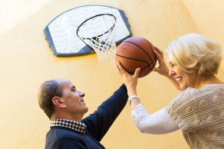 Happy active mature couple playing basketball in patio photo