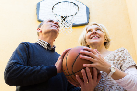 Happy smiling active couple of pensioners playing basketball in patio photo