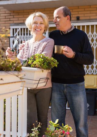 balcon: Elderly positive woman talking with male neighbor at balcon