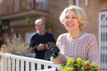 horticultural: Joyful smiling mature woman with horticultural sundry and aged man drinking tea in patio Stock Photo