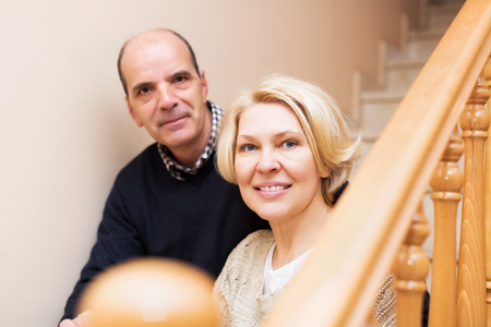 spouses: Happy mature spouses leaning against stairway indoor