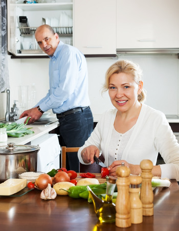 spaniard: happy mature couple cooking Spaniard tomatoes at home kitchen Stock Photo