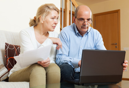 wistful: Senior man with mature wife reading business documents and using laptop in home interior