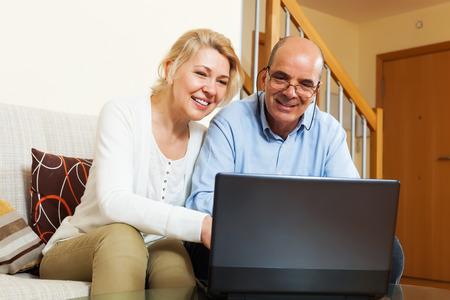 mujeres mayores: Pareja madura con el ordenador portátil en la mesa en casa Foto de archivo
