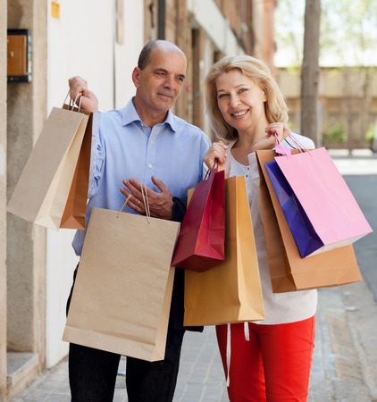 after shopping: Positive mature family with bags after shopping at street Stock Photo
