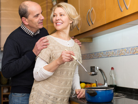 spouses: Smiling happy senior spouses preparing meal at modern kitchen Stock Photo