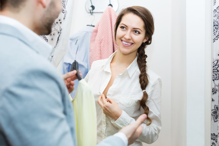 cubicle: Smiling adult spouses standing at boutique changing cubicle Stock Photo