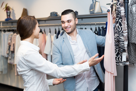 purchaser: Store clerk serving purchaser at fashionable apparel store. Selective focus on girl