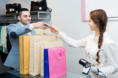 store clerk: Smiling store clerk serving purchaser at cash register desk Stock Photo
