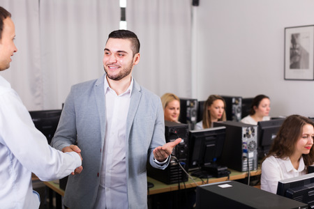 thanking: Friendly smiling boss greeting new colleague at office Stock Photo