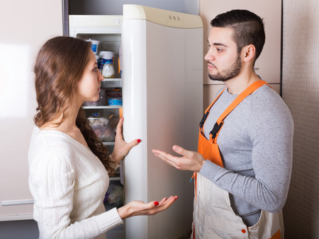 aftersales: Young housewife showing broken refrigerator to serious repairman Stock Photo