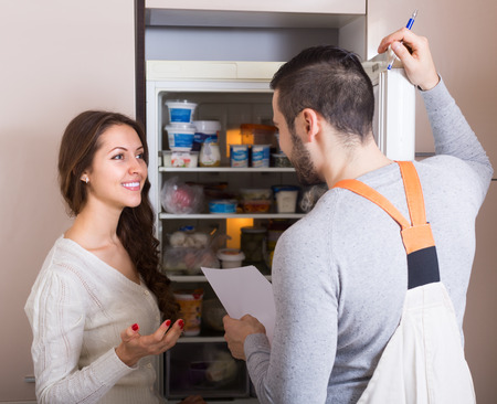 aftersales: Workman visiting housewife for after-sales service of refrigerator