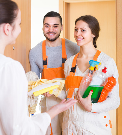 communal: Housewife meeting cleaning crew with equipment at doorway. Focus on girl Stock Photo