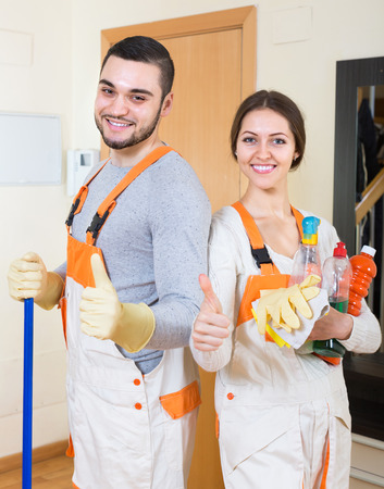 Portrait of cleaning premises team with equipment standing at doors of client house Stock Photo