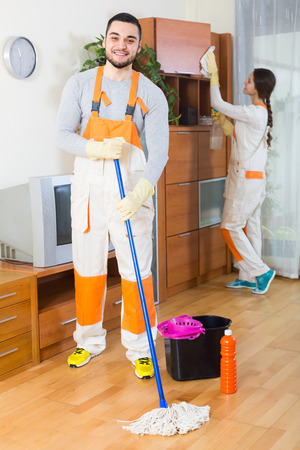 premises: Portrait of smiling cleaning premises team with equipment working at client house. Focus on man Stock Photo