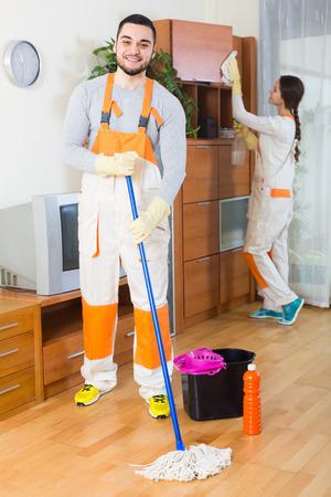 cleaning team: Retrato de sonriente equipo de limpieza de los locales con un equipo de trabajo en la casa del cliente. Centrarse en el hombre