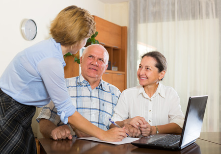 census: Smiling mature couple 60s years old discussing employee of  company at home Stock Photo