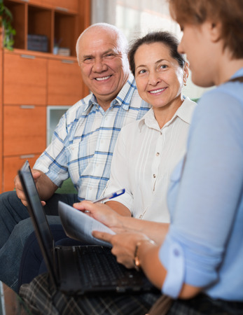 work worker: Mature couple answer questions of caseworker with computer in office