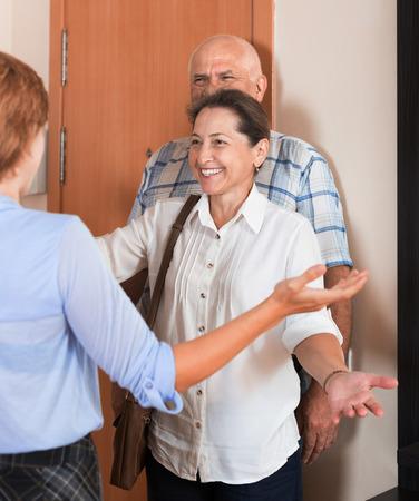 threshold: Positive daughter greeting elderly parents at threshold