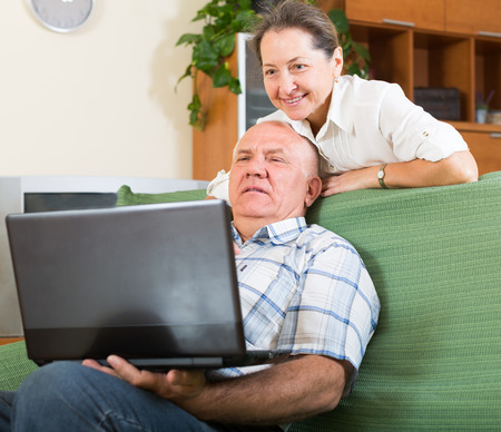 Happy elderly cheerful man and mature woman using laptop at home photo