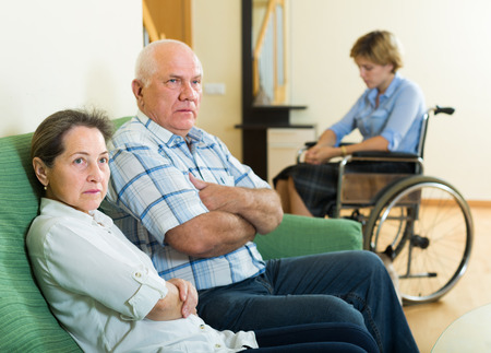 Communication problems between woman in wheelchair and aged relative. Focus on woman