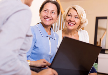 old document: Banking agent explaining to female pensioners finance plan Stock Photo