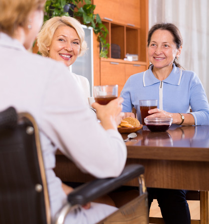 Mature female pensioners drinking tea with handicapped friend. Focus on the left woman photo