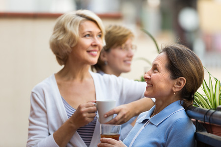satisfied people: Three smiling mature women drinking tea with cookies at balcony. Focus on brunette