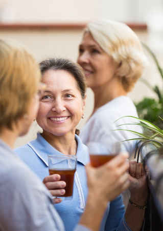 mature women: Three positive smiling mature women staying on balcony with tea. Focus on brunette Stock Photo
