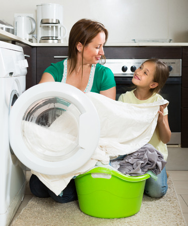 work clothes: Home family laundry. Smiling mother with little daughter loading clothes into washing machine in kitchen. Focus on woman Stock Photo