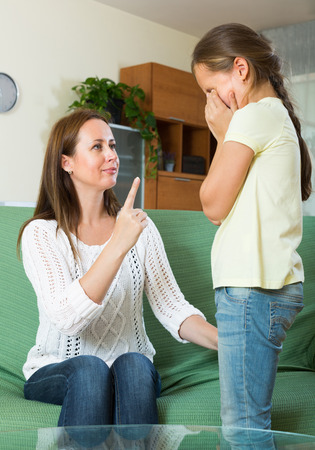 Mother berating  crying schoolgirl at interior