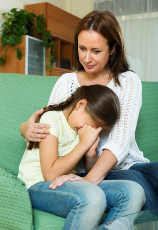 home comforts: Woman comforting sad  crying daughter at home
