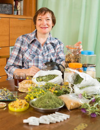 concoct: Smiling mature woman with herbs at table in home