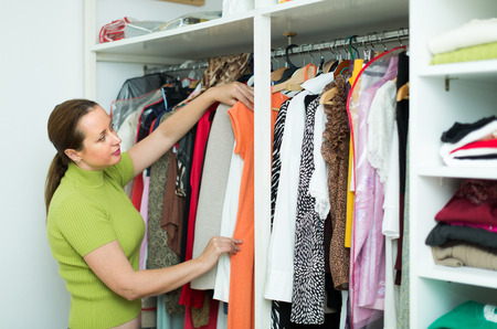 Happy housewife checking apparel at family cloakroom