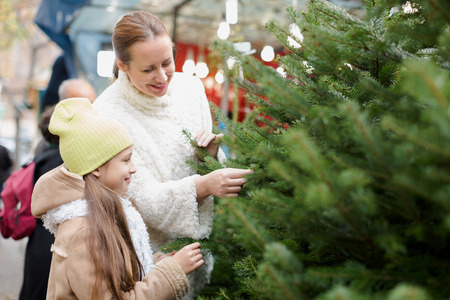 christmas shopping: woman with her smiling daughter buying Christmas tree in market. Focus on girl