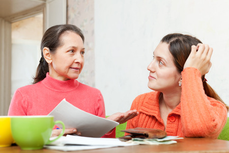 mother berates adult daughter for payments bills or credits. Focus on mature photo