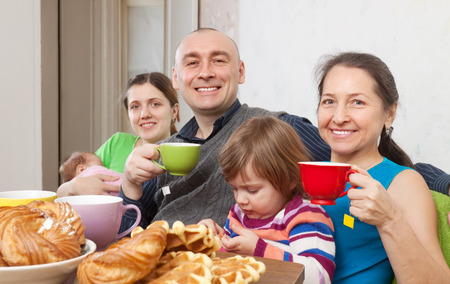 gladful: Happy family having tea and cakes at home Stock Photo