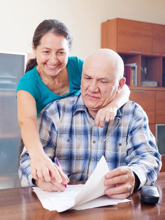 fills: Elderly man fills the paper documents, woman watching him Stock Photo