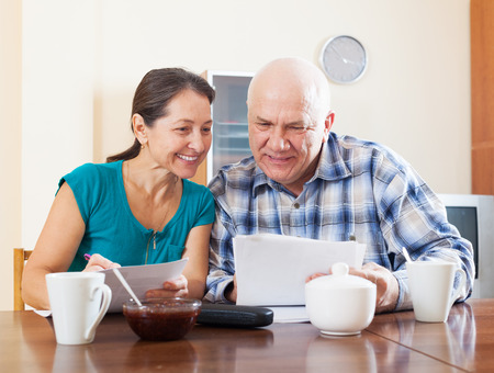 Smiling mature couple reading documents during tea at home interior Stock Photo