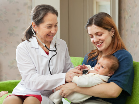children's doctor: doctor examining newborn baby on mothers arms Stock Photo
