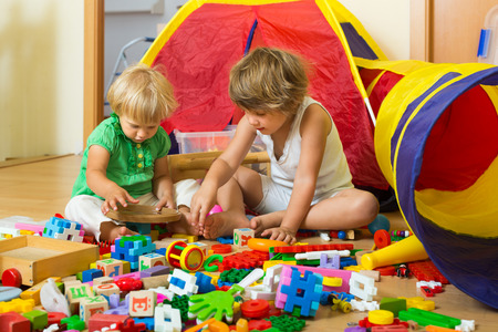 quiet baby: Calm children playing with toys in home interior